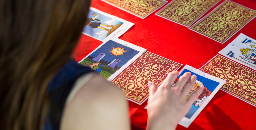 person reading a Tarot spread on a red table